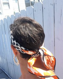 A back view of the head of a woman with short brunette hair. She is wearing gold hoop earrings and a vintage silk scarf with a black, white, and orange houndstooth pattern on it that is around her head and tied at the back
