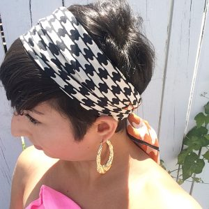 A side view of a woman with short brunette hair. She has on gold hoop earrings and a vintage silk scarf with a black, white, and orange houndstooth pattern on it that is around her head and tied at the back