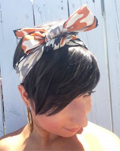 The top view of a woman's head. She has short brunette hair that covers one of her eyes and is wearing gold hoop earrings and a vintage silk scarf with a black, white, and orange houndstooth pattern on it that is around her head and tied at the top in a bow