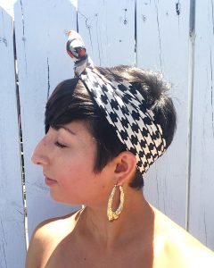 A side view of a woman with short brunette hair. She has on gold hoop earrings and a vintage silk scarf with a black, white, and orange houndstooth pattern on it that is around her head and tied at the top in a bow