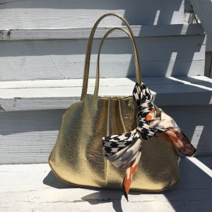 A picture of a gold purse with a vintage silk scarf with a black, white, and orange houndstooth pattern on it tied around one of the handles of the purse