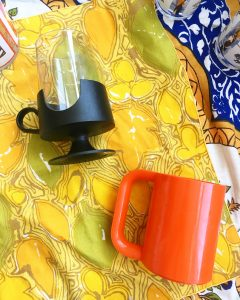 A picture of two mid-century, modern, 70's styled cups. One is all orange and blocky with a large handle and the other is glass with a black bottom and smaller handle. Both cups are laying on their sides on top of a yellow patterned table cloth
