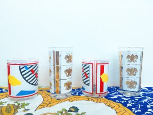 A picture of four cups sitting on top of an ornate classical table cloth. Two of the cups are short, bourbon-style, art deco, pop art cups and two of the cups are tall gold and white printed with fleur de lis on them.