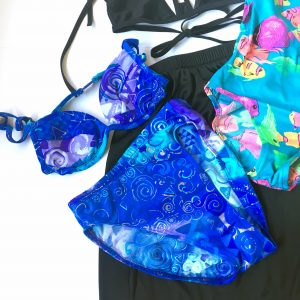 A picture of a blue, high waisted bikini with different 90's patterns on it, a one piece bathing suit that is a turquoise color with hot pink tropical fish on it, and a black bikini top and a black skirt with a pastel boarder. This particular picture focuses on the blue two piece bathing suit