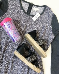 A close up of the dark gray and white, long-sleeved, patterned, Lou & Grey summer dress in a size large, a pink, purple, and light blue Lilly Pulitzer tumbler cup, and a pair of black and tan woman's sandals.
