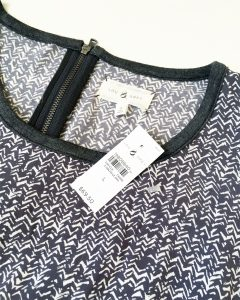 A picture of the tag of the dark gray and white, long-sleeved, patterned, Lou & Grey summer dress in a size large. The tag says the dress originally sold for $69.50