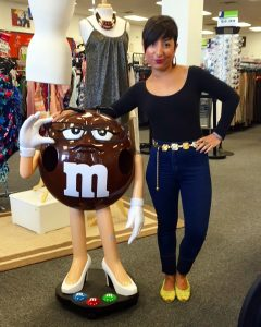 A picture of a woman in a black, long sleeved top, blue jeans, and neon shoes standing next to a large brown M&M figurine