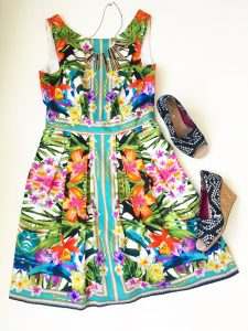 A picture of a sleeveless, bright, Maggy London dress with a tropical floral pattern on it. Next to the dress is a pair of black and white Aztec triangle patterned TOMS wedge open toed shoes.