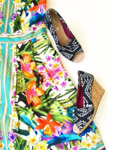 A close up of the pair of black and white Aztec triangle patterned TOMS wedge open toed shoes. These are next to the tropical floral patterned Maggy London dress
