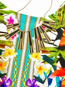 A close up of a black and gold piano key necklace on top of the tropical floral patterned Maggy London dress