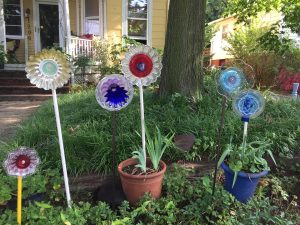"Six DIY flowers made from plates, jello molds, glass wear in different colors sitting ""planted"" outside of a yellow house"