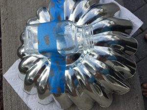 A picture of a clear salt shaker being glued to the bottom of a metal jello mold being held in place by blue painters tape