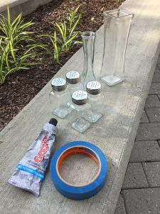 A picture of a tube of glue, blue painters tape, some clear vases, and four salt and pepper shakers sitting on a concrete wall