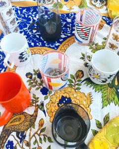 A top down view of all of the cups mentioned in this post. There are two of the art deco bourbon glasses, one of the orange block mugs, one of the glass with a black bottom and smaller handle, two of the white mugs with daisys on them, and one of the gold and white printed taller glasses with fleur de lis on them