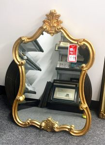 A wall mirror with an ornate, gold, boarder frame
