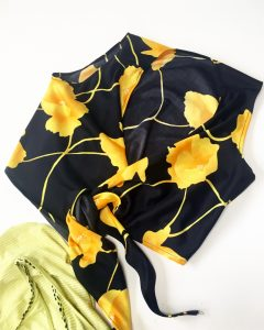 A black crop top with yellow flowers on it. It has a sheen and ties in the back