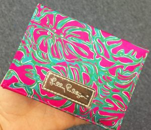 A picture of a woman holding a Lilly Pulitzer clutch purse. It has pink palm leaves against a green and aqua background. The Lilly Pulitzer logo is on a leather rectangle that is sewn to the clutch