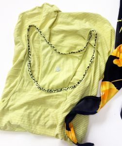 Lululemon striped yellow tank top with a yellow and black leopard print lining around the collar. It is folded in half