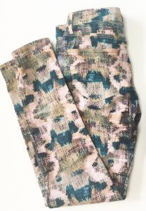 A pair of patterned Madwell pants. The pattern looks painted on and has the colors blue, pink, black, olive green, and a light peach color