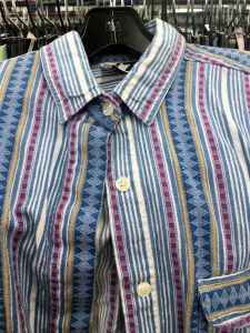 A picture of a vintage, 1990's, button up top. It has a few shades of blue and pink and has vertical stripes in different patterns. This is a close up of the buttons and collar