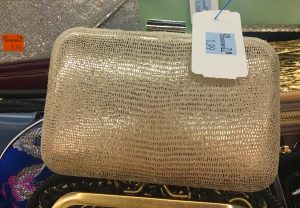 A picture of a gold, almost snake skin rigid clutch purse. It has a Goodwill tag on it that states it is $1.99