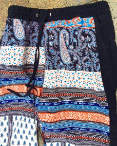 A pair of ornately patterned Topshop pants. They have the colors orange, blue, navy, light blue, and white. They have a drawstring at the top.