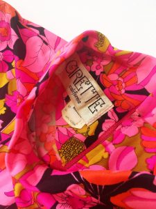 A pink, floral, sleeveless dress with a pair of green jelly flat shoes. This picture is a close up of the tag
