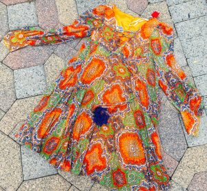 An ornately patterned 1970's Howard Hirsch dress. It has the colors yellow, orange, red, green, and purple, has a tie at the neckline and the sleeves flair at the end.
