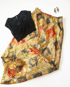 A picture of three items: a black shirt, a pair of black, geometric crystal earrings, and a metallic gold, black, and red patterned material and lined with a cream fabric maxi dress