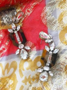 A pair of black and clear gem J Crew earrings. The gems are in different geometric shapes and the earrings dangle. They are sitting on top of a very close up picture of the gold, red, and black patterned Nelly de Grab maxi dress