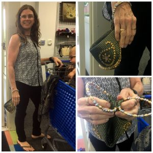 A collage of three pictures: the larger one on the left is of a woman in glasses, a sleeveless shirt, and black pants standing next to a blue shopping cart with a baby in it holding a small ornate clutch. The picture on the top right is a close up of the ornate, green clutch with gold beads and a silver and gold handle and the picture on the bottom right is a closer look at the clutches' handle