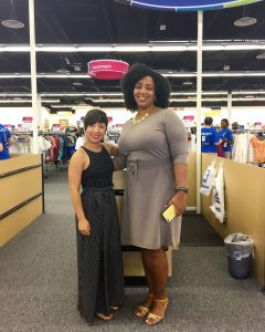 A picture of the DC Goodwill Fashionista (a short woman with short brown hair in a sleeveless black jumpsuit) and Danielle from Perfectly Good blog (a taller African American Woman in a grey dress with a yellow necklace) standing in front of the check out registers at the Centreville, VA Goodwill retail store