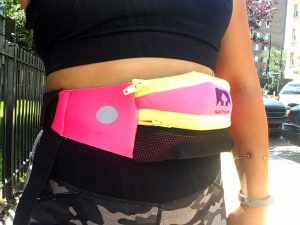 A picture of the midsection of a woman. She is wearing a black running bra, grey and black camo workout pants, and a pink Nathan fanny pack with bright yellow zippers