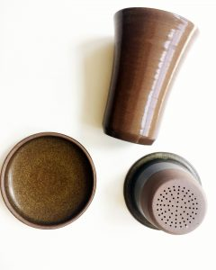 A picture of various pieces of a brown, ceramic, tea infuser