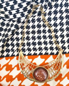A necklace with a round, amber stone surrounded by a lattice of gold and a gold chain. This is on top of a black, orange, and white hounds tooth scarf