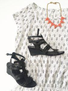 A picture of a white Joie day dress. It has a small, black, design all over it in rows that almost look like small bird's feet. The dress has very short sleeves and gets smaller around the waist. Also pictured is an orange necklace with rine stones. Also pictured is a pair of black, wedge sandals.
