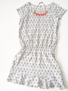 A picture of a white Joie day dress. It has a small, black, design all over it in rows that almost look like small bird's feet. The dress has very short sleeves and gets smaller around the waist. Also pictured is an orange necklace with rine stones
