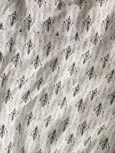 A close up of the pattern of the white Joie day dress. It has a small, black, design all over it in rows that almost look like small bird's feet. The dress has very short sleeves and gets smaller around the waist.