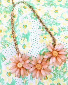 A necklace with a gold chain that connects to three pink flowers that are made of rine stones. It is on top of a light green and yellow floral scarf