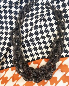 A necklace with that has a thick, gunmetal, woven chain necklace. It is on top of a black, orange, and white hounds-tooth scarf