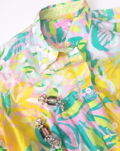 Close up of the top portion of a Lilly Pulitzer Hawaiian style shirt. The shirt is colored in bright yellow, green, aquas, and pinks and has a pair of crystal like dangle earrings on top of it.