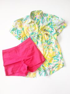 A Lilly Pulitzer Hawaiian style shirt. The shirt is colored in bright yellow, green, aquas, and pinks. With the shorts is a pair of bright pink shorts