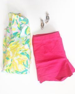 A Lilly Pulitzer Hawaiian style shirt. The shirt is colored in bright yellow, green, aquas, and pinks. With the shorts is a pair of bright pink shorts. The shirt and shorts are folded up. There is also a pair of crystal like dangle earrings
