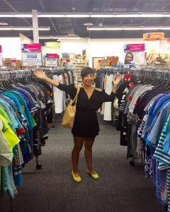The DCGF (a woman with short, black hair in a short black dress and neon yellow shoes, stands between two racks of clothing in the Goodwill of Greater Washington Sully Station store