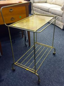 A gold bar cart made of brass. It has two levels and has black swivel wheels