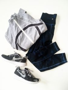 A picture of three objects: a grey Lululemon zip up jacket with a blue stripe through the middle of it, a pair of Lululemon blue workout pants, and a pair of Nike grey and black sneakers