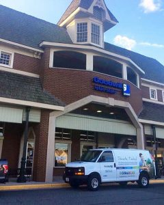 The storefront of the Goodwill of Greater Washington retail store and donation center located in the Sully Station Shopping Center in Centreville, VA. The Goodwill marketing van, wrapped in Goodwill branding, is parked outside the front