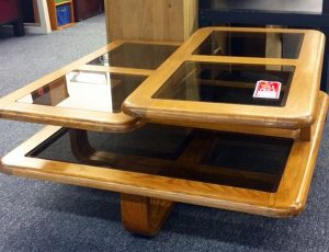A layered wooden coffee table with square glass paneling