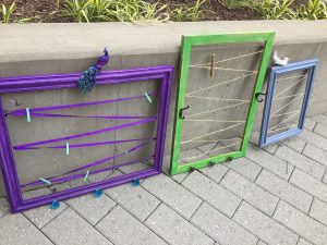 A picture of three frames with the glass and backing taken out and replaced with a zig zag ribbon to hang items on. There is a purple one with a bird sitting on top, a green one in the middle, and a third light blue one on the right with a small white bird on it.