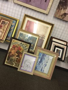 A picture of various pictures and frames at a Goodwill store